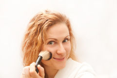 Attractive woman doing make-up on face. Royalty Free Stock Photos