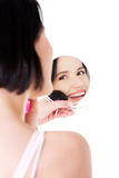 Attractive woman doing make-up on face. Stock Photography