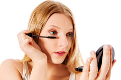 Attractive woman doing make-up on face. Isolated Stock Photos