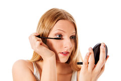 Attractive woman doing make-up on face. Isolated Royalty Free Stock Photo