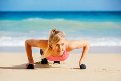 Attractive woman doing push ups outside. Royalty Free Stock Images
