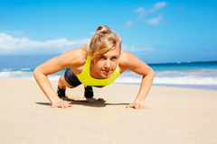 Attractive woman doing push ups outside. Stock Image