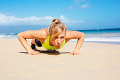 Attractive woman doing push ups outside. Young attractive woman doing push ups outside. Fitness woman working out at the beach. Crossfit exercise. Fitness stock image