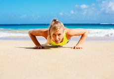 Attractive woman doing push ups outside. Young attractive woman doing push ups outside. Fitness woman working out at the beach. Crossfit exercise. Fitness stock images