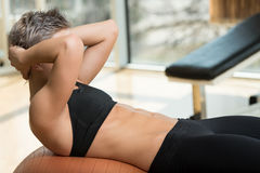 Attractive Woman Doing Sit-Ups With Exercise Ball. Exercising Abdominals In Fitness Club Royalty Free Stock Images
