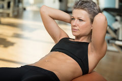 Attractive Woman Doing Sit-Ups With Exercise Ball. Exercising Abdominals In Fitness Club Royalty Free Stock Photo