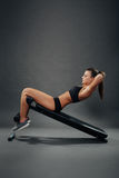 Attractive woman doing sit ups on incline bench Royalty Free Stock Photo