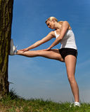 Attractive woman doing stretching exercise outside Stock Image