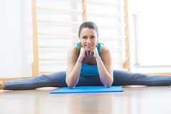 Attractive woman doing stretching exercises at gym Stock Images