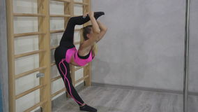 Attractive woman doing stretching legs standing in sports club indoor. stock video