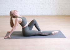 Attractive woman in gray sport wear sitting on mat and bending her back in yoga studio, selective focus stock images