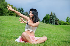 Attractive woman doing yoga. With  does ridiculously by hands and laughs on beautiful green lawn Stock Photo