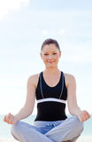 Attractive woman doing yoga exercises on the beach Stock Photos