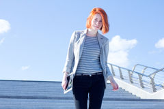 Attractive woman down the stairs with tablet against the sky Stock Image