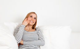 Attractive woman dreaming on a sofa Royalty Free Stock Photography