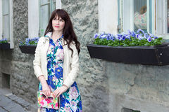 Attractive woman in dress with beautiful flowers in old town Stock Image