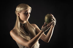 Attractive woman in dress holding a dragon egg in hands. Isolated on black Royalty Free Stock Image