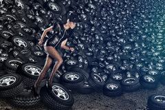 Attractive woman in dress running. On tires Royalty Free Stock Photography