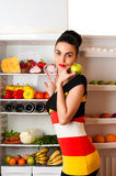 Attractive woman in dress standing at the fridge. Isolated on white background Royalty Free Stock Photos