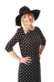 Attractive woman in dress. Young attractive woman wearing a black spotted dress with a black hat. White background Royalty Free Stock Photos