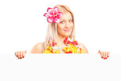 Attractive woman dressed in a hawaiian costume holding a panel Royalty Free Stock Images