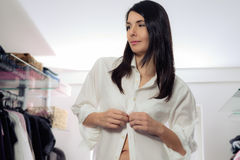 Attractive woman dressing in a dressing room. Attractive young brunette woman standing dressing in a walk in dressing room buttoning up her clean white shirt Stock Image