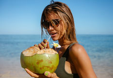 Attractive woman drinking coconut water on the beach Stock Photos