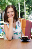 Attractive woman drinking coffee. Attractive woman drinking a cup of cappucino coffee seated outdoors at a table in her garden Stock Photography