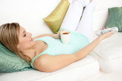 Attractive woman drinking a coffee at home. Attractive woman drinking a coffee while watching TV lying on a sofa stock image