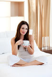 Attractive woman drinking coffee sitting on bed Stock Photo