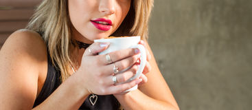 Attractive woman drinking a hot beverage royalty free stock photo