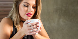 Attractive woman drinking a hot beverage stock image
