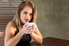 Attractive woman drinking a hot beverage royalty free stock image