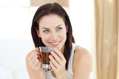 Attractive woman drinking tea. Sitting on her bed Stock Photos