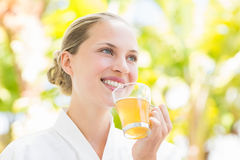 Attractive woman drinking tea. In a glass at spa center Stock Photography