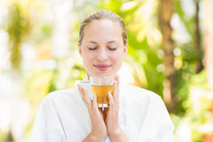 Attractive woman drinking tea. In a glass at spa center Stock Photos