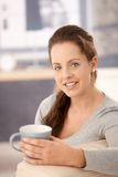 Attractive woman drinking tea on sofa smiling Stock Photos