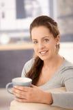 Attractive woman drinking tea on sofa smiling Stock Photos