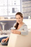 Attractive woman drinking tea on sofa smiling Stock Images