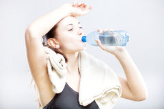 Attractive woman drinking water after fitness class stock images