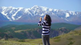 Beautiful young woman traveler drinks water on a background of beautiful mountains. 4k Woman relaxes on the top of the stock video footage