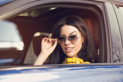 Attractive woman driver with sunglasses sitting inside her car stock photos