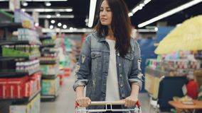 Attractive woman is driving shopping trolley through food department in supermarket and looking around. Pretty girls. Attractive young woman is driving shopping stock footage
