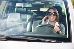Attractive woman driving and talking on the phone Royalty Free Stock Images