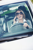 Attractive woman driving and talking on the phone Stock Photos