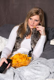 Attractive woman is eating chips and has remote control in hand Stock Photo