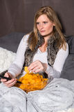 Attractive woman is eating chips and has remote control in hand Royalty Free Stock Photos