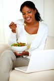 Attractive woman eating healthy salad. Portrait of an attractive woman eating healthy salad while is sitting on couch in front of her laptop Stock Photos