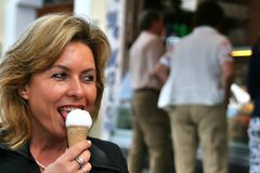 Attractive woman eating ice cream in front of an italian ice cream parlor, Gelateria Stock Photo