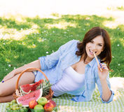 Attractive woman eating a pretzel stick lying on a mat Stock Photography